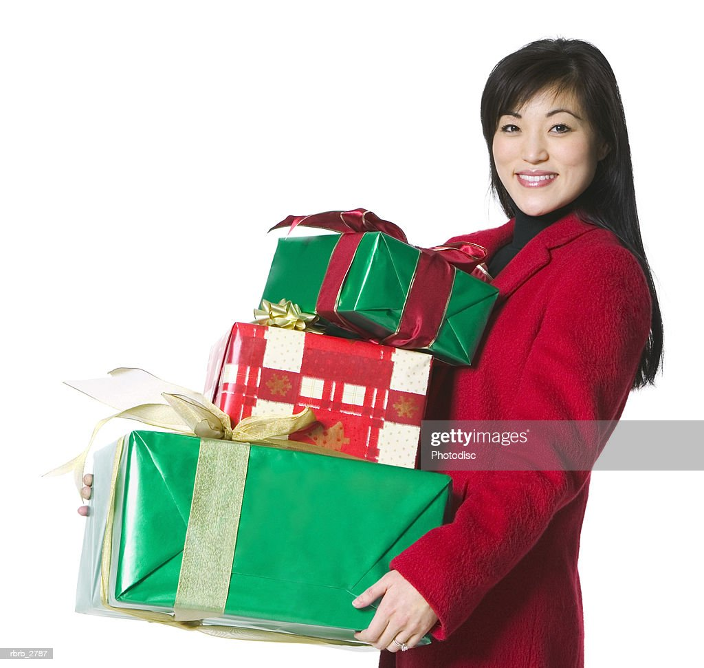 portrait of a young adult female in a red coat as she carries some christmas presents : Foto de stock