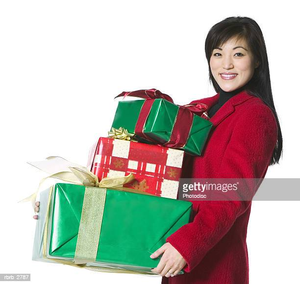 portrait of a young adult female in a red coat as she carries some christmas presents