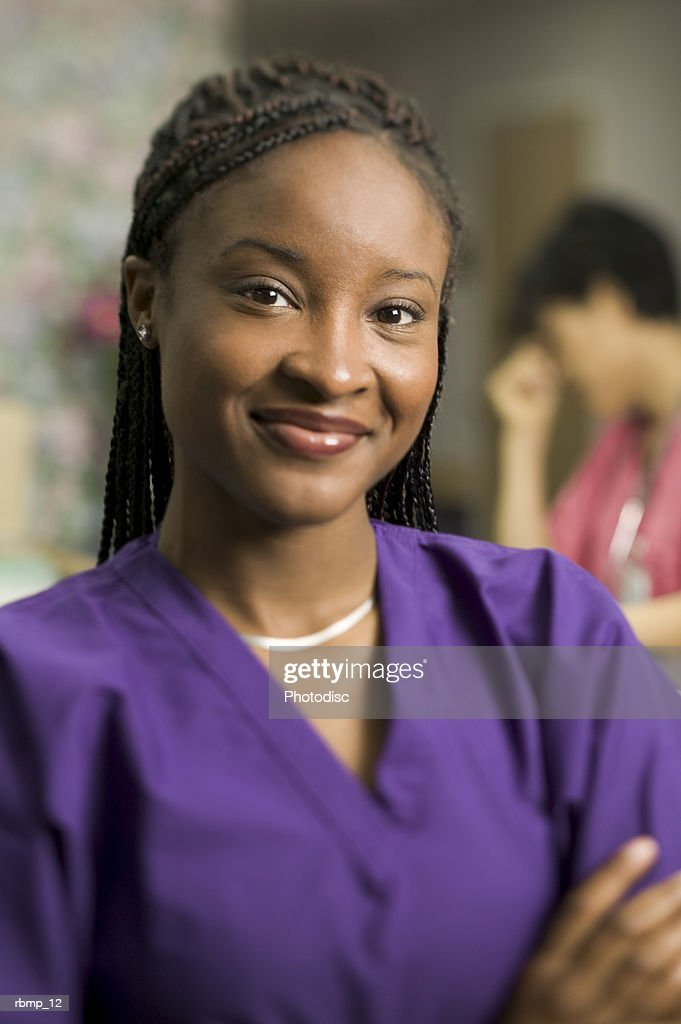 portrait of a young adult female in purple scrubs standing by the nurses station as she smiles : Stockfoto