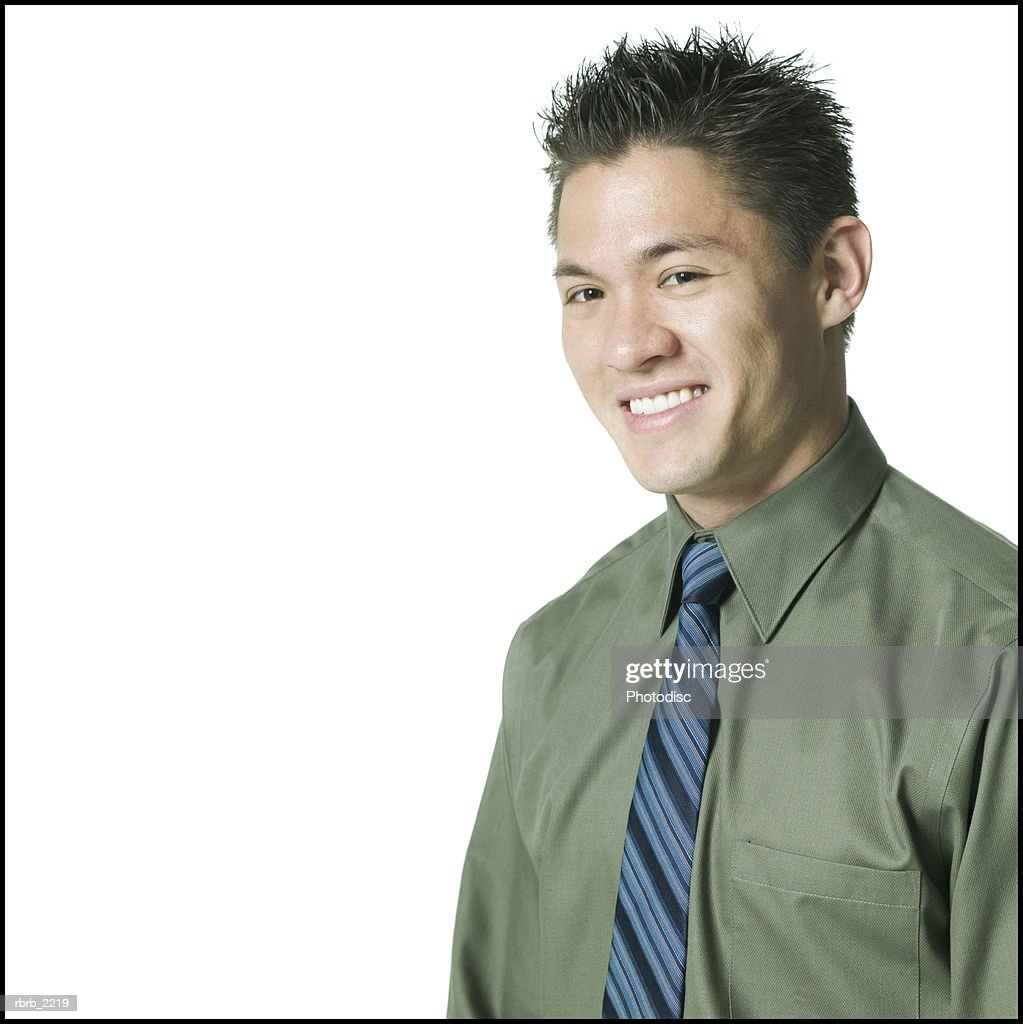 portrait of a young adult male in a green shirt and tie as he grins at the camera : Foto de stock