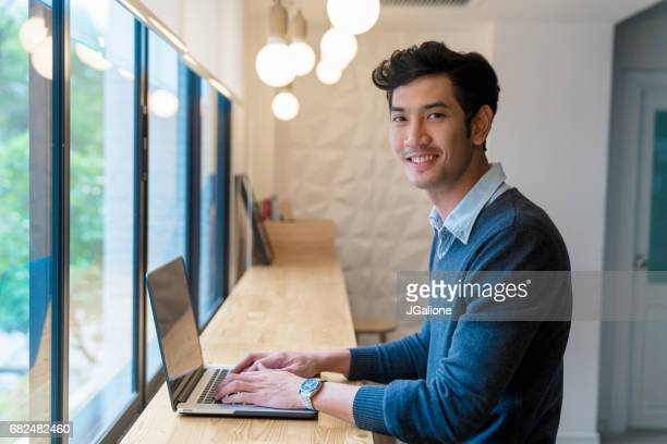 portrait of a young adult male sat using his laptop in a modern office - east asian culture stock photos and pictures