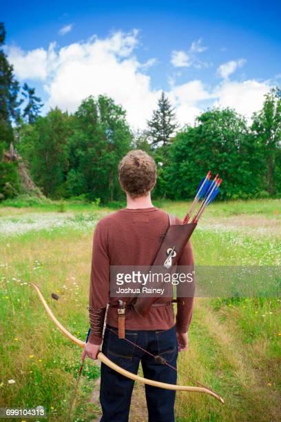 portrait of a young adult male with archery gear outdoors - arco arco e flecha - fotografias e filmes do acervo