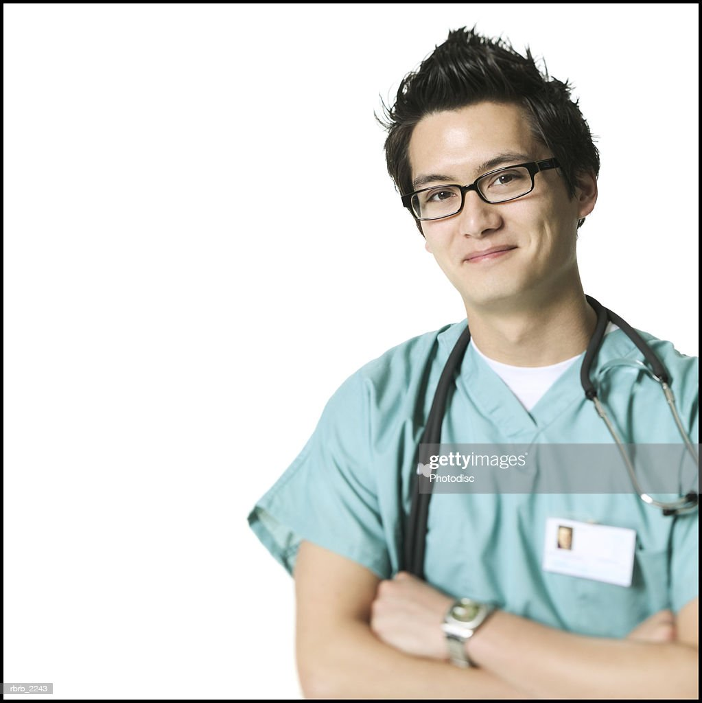 portrait of a young adult man in green scrubs as he folds his arms and smiles at the camera : Foto de stock