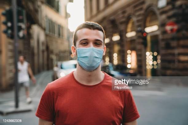 ritratto di un giovane adulto che indossa una maschera protettiva per il viso e guarda la macchina fotografica - uomini giovani foto e immagini stock