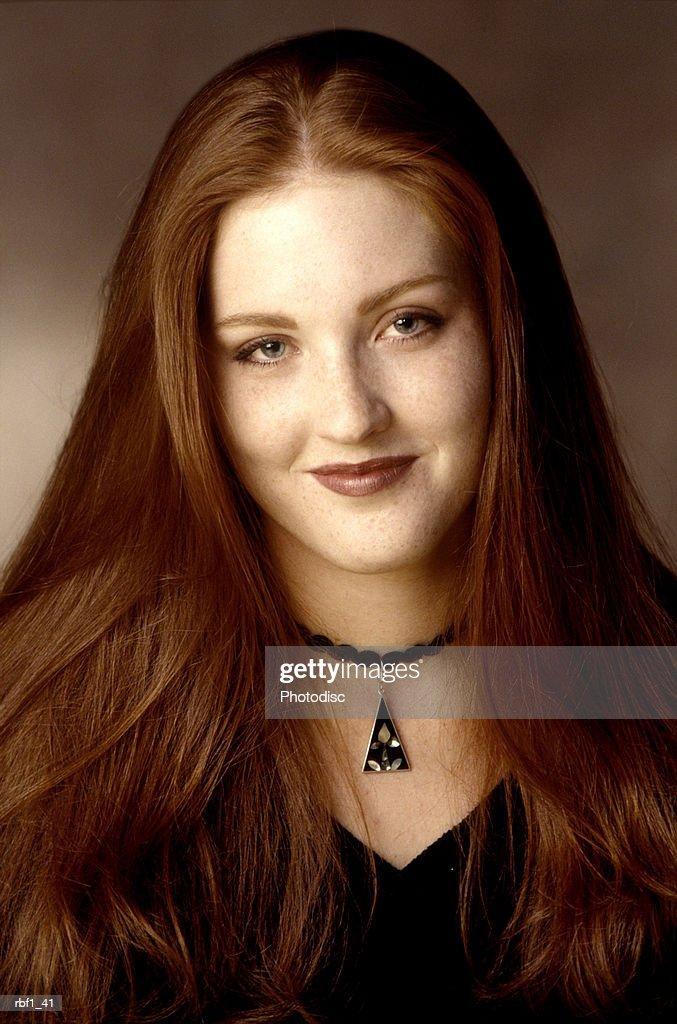 portrait of a young adult redheaded woman in a black sweater as she smiles at the camera : Stockfoto