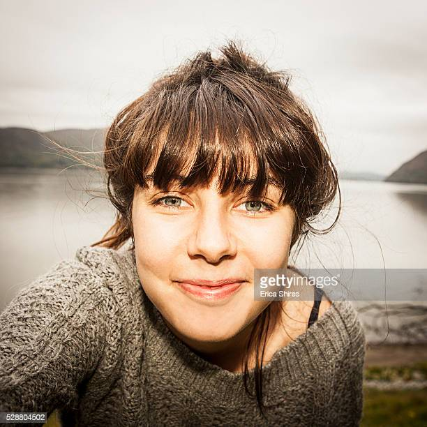 portrait of a young adult woman at lakeside - brune aux yeux bleus photos et images de collection