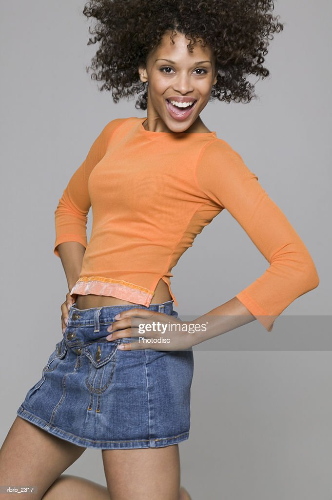 portrait of a young adult woman in an orange shirt as she playfully jumps around : Foto de stock