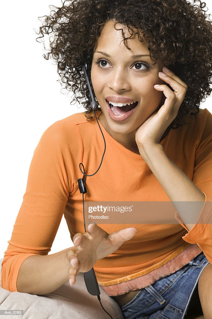 portrait of a young adult woman in an orange shirt as she talks on a hands free phone set : Foto de stock