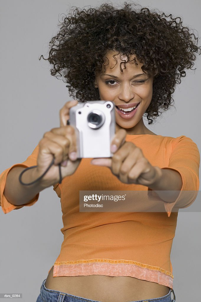 portrait of a young adult woman in an orange shirt as takes a picture with a digital camera : Foto de stock