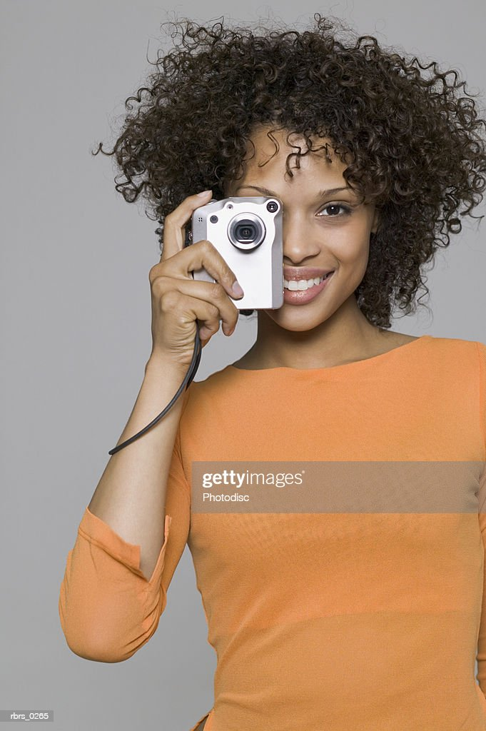 portrait of a young adult woman in an orange shirt as takes pictures with a digital camera : Foto de stock