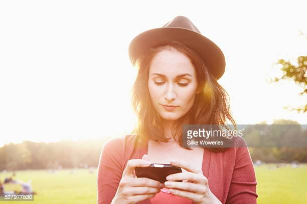 portrait of a young adult woman texting on her mobile phone outside in a park, backlit. - search engine stock pictures, royalty-free photos & images