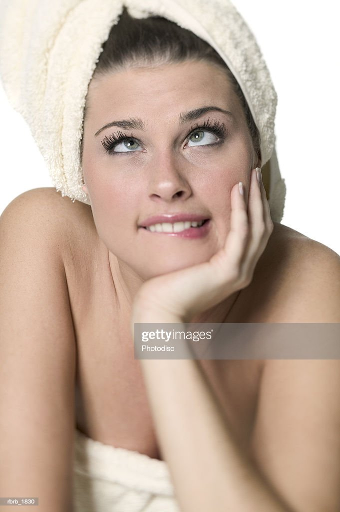 portrait of a young adult woman with her hair wrapped in a towel as she rolls her eyes : Stockfoto