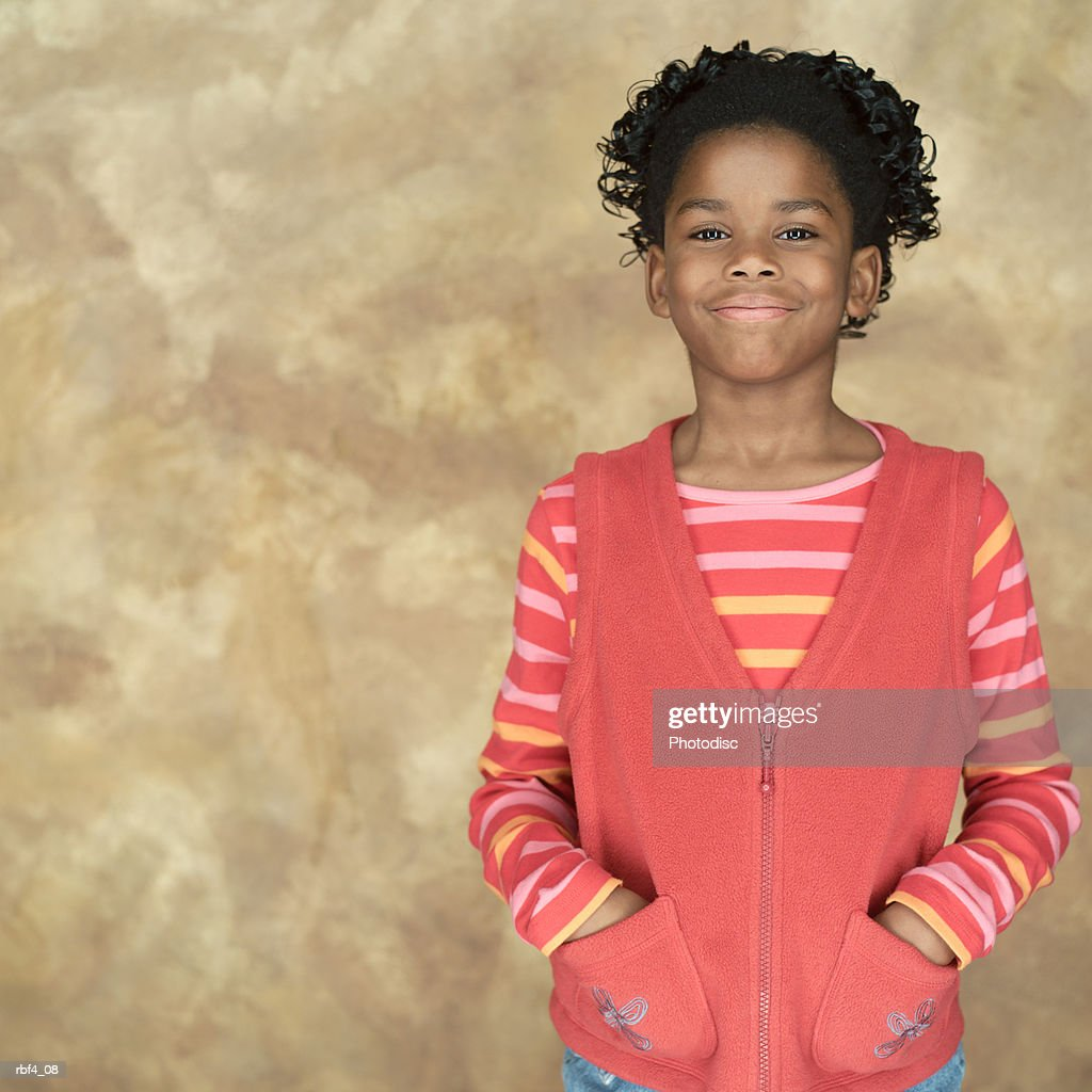 portrait of a young african american girl in a pink shirt and sweater as she puts her hands in her pockets and smiles : Stock Photo