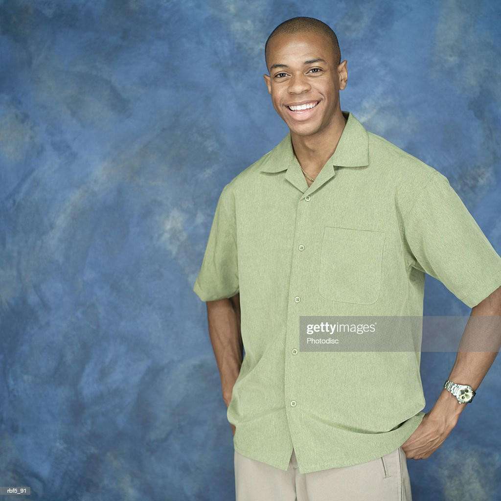 portrait of a young african american man in a green shirt and tan pants puts his hands on his hips and smiles : Stock Photo