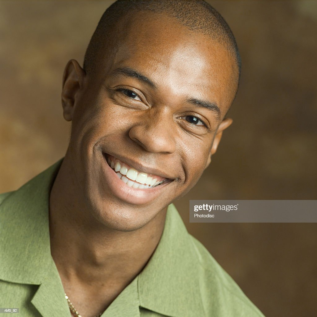 portrait of a young african american man in a green shirt as he smiles big into the camera : Stockfoto