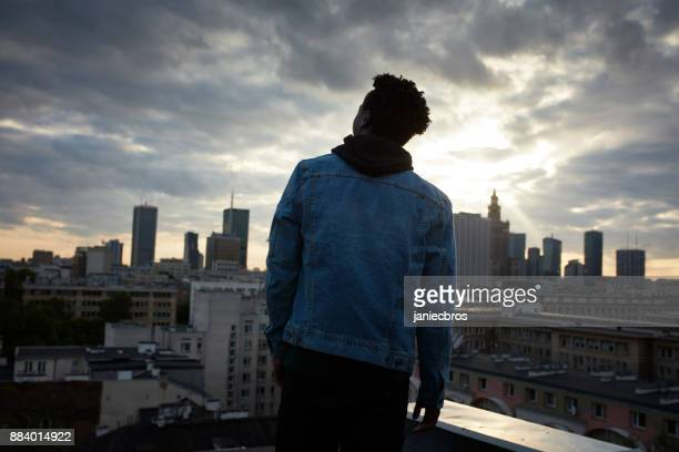 portrait of a young african man. urban skyline in background - black jacket stock pictures, royalty-free photos & images