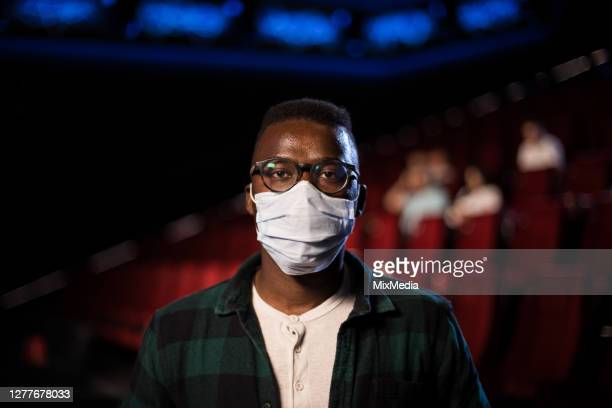 portrait of a young african-american man with a protective mask at the cinema - film festival stock pictures, royalty-free photos & images
