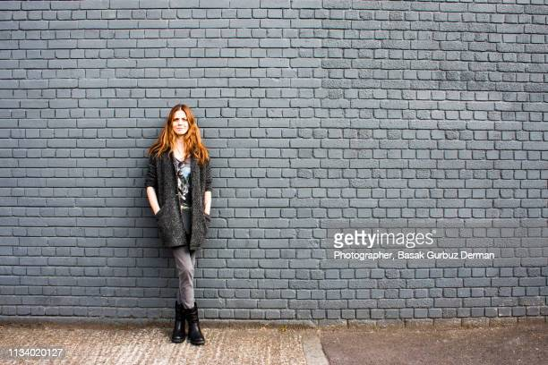 portrait of a young and confident woman leaning against a brick wall - gray jeans stock pictures, royalty-free photos & images