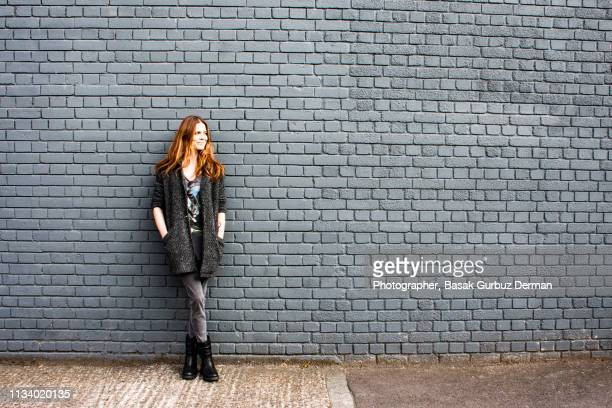 portrait of a young and confident woman leaning against a brick wall - ブーツイン ストックフォトと画像