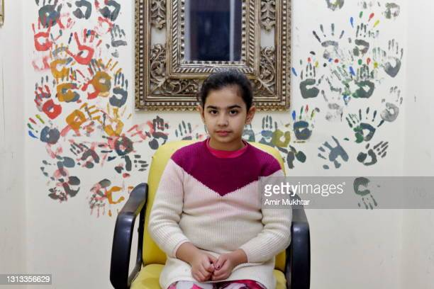 a portrait of a young artist girl infront of her colorful hand prints painting on wall. - pakistan stock pictures, royalty-free photos & images