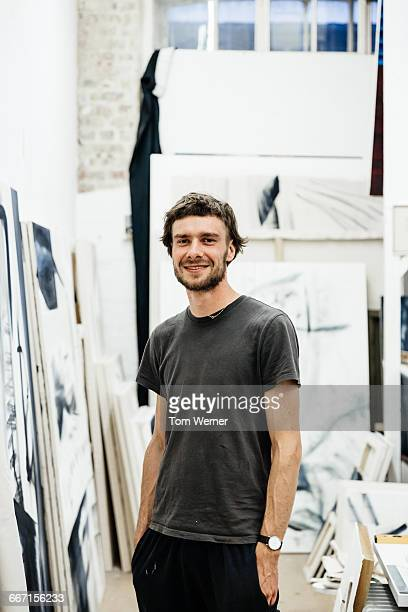 portrait of a young artist standing in his atelier - dreiviertelansicht stock-fotos und bilder