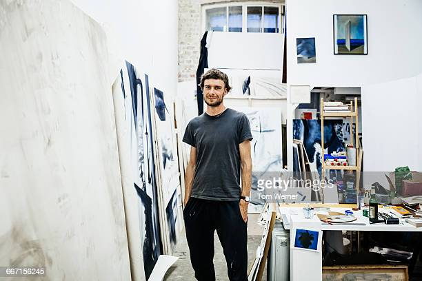 Portrait of a young artist standing in his atelier