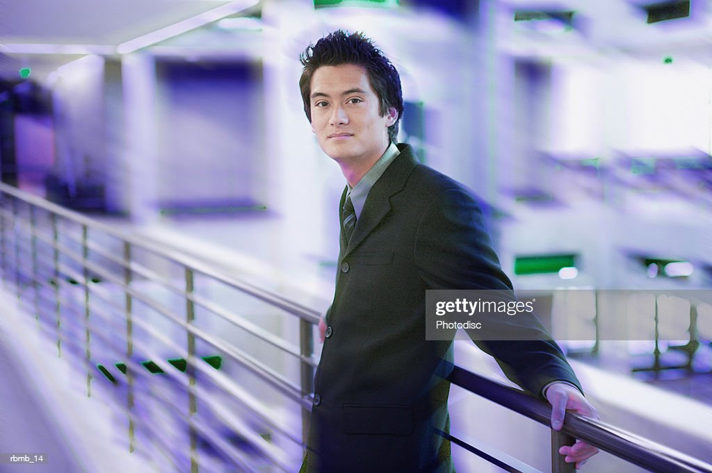 portrait of a young asian business man in a dark suit as he laens against a railing : ストックフォト