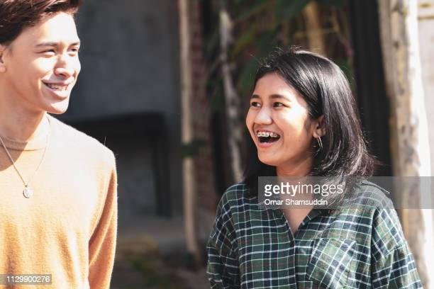 Portrait of a young Asian girl laughing with a friend outdoor