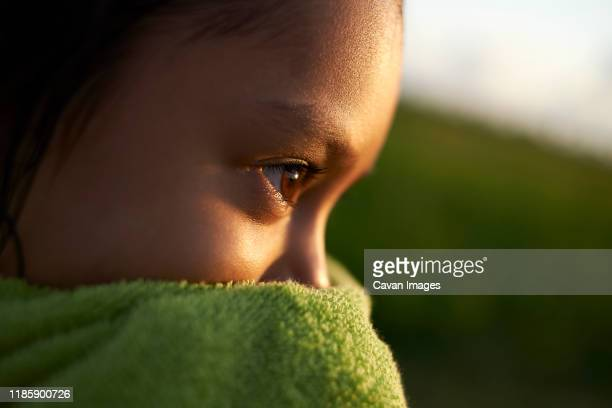 portrait of a young asian girl wrapped in a green towel at sunset - towel stock pictures, royalty-free photos & images