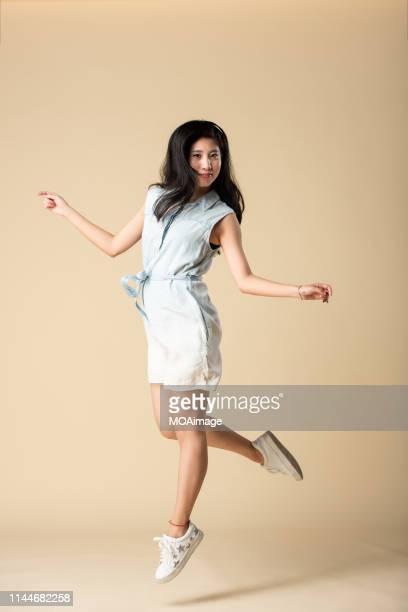 portrait of a young asian lady in a studio shot - sauter photos et images de collection
