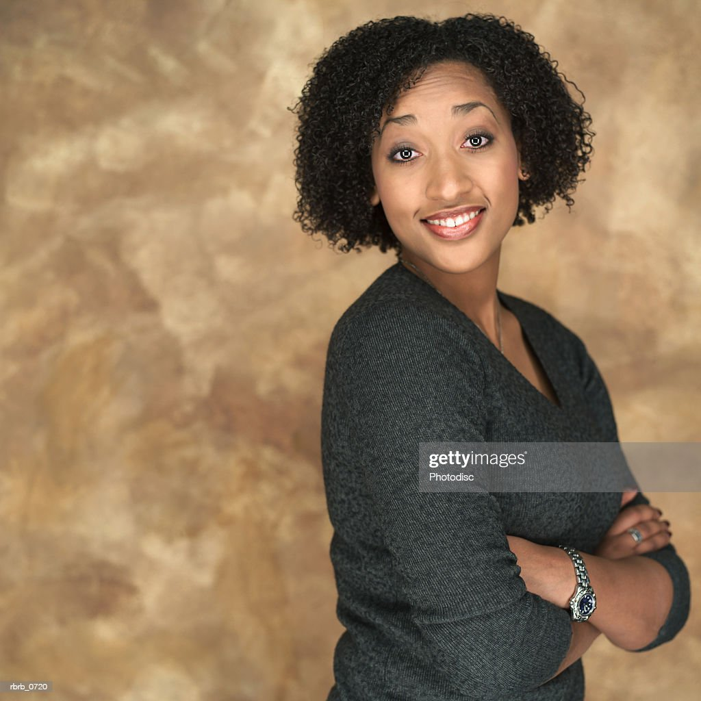 portrait of a young attractive african american woman as she fold her arms and smiles : Stockfoto