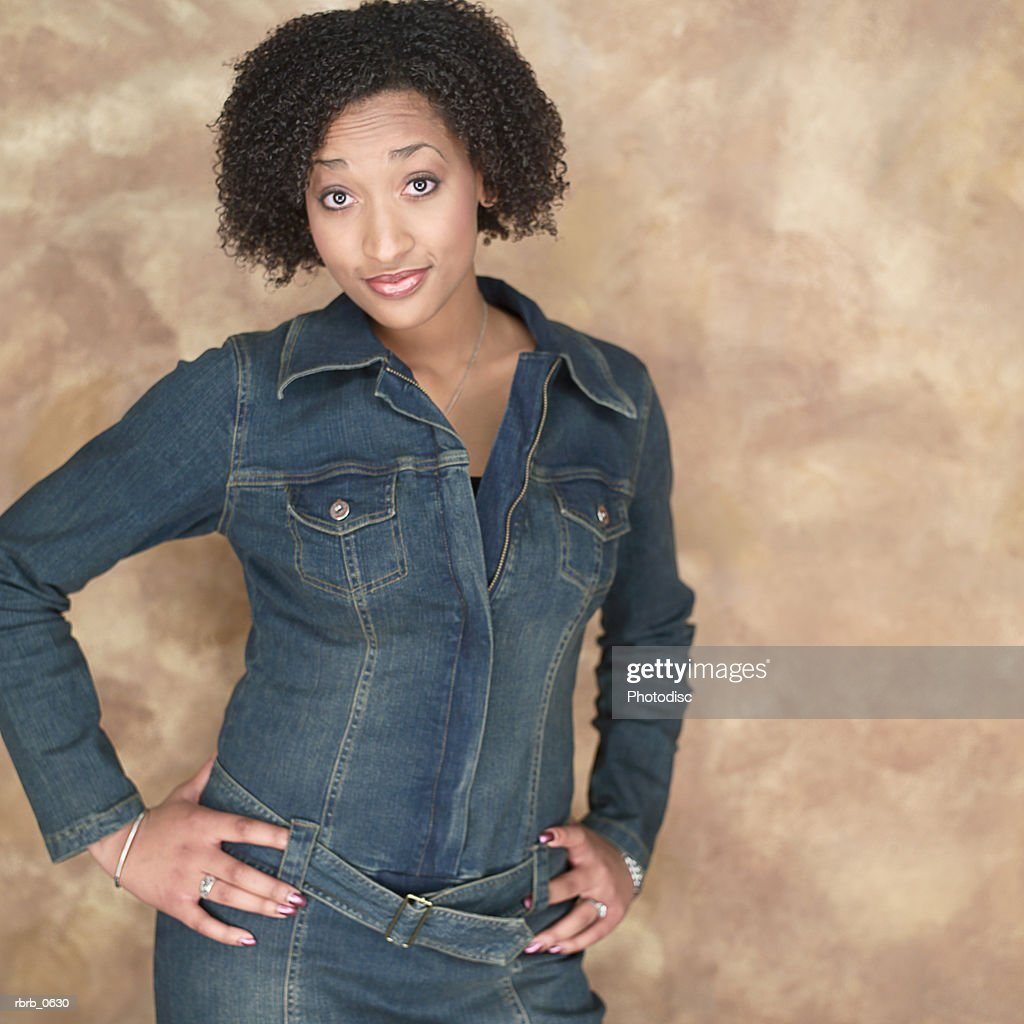 portrait of a young attractive african american woman in a denim outfit as she flashes some attitude : Bildbanksbilder