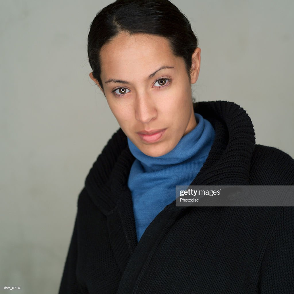 portrait of a young attractive ethnic woman as she turns and looks seriously into the camera : Stockfoto