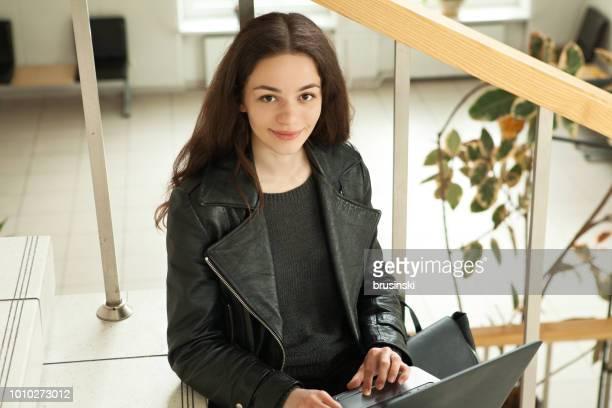 Porträt einer jungen attraktiven Frau 18 Jahre arbeiten mit einem Laptop in einem öffentlichen Gebäude