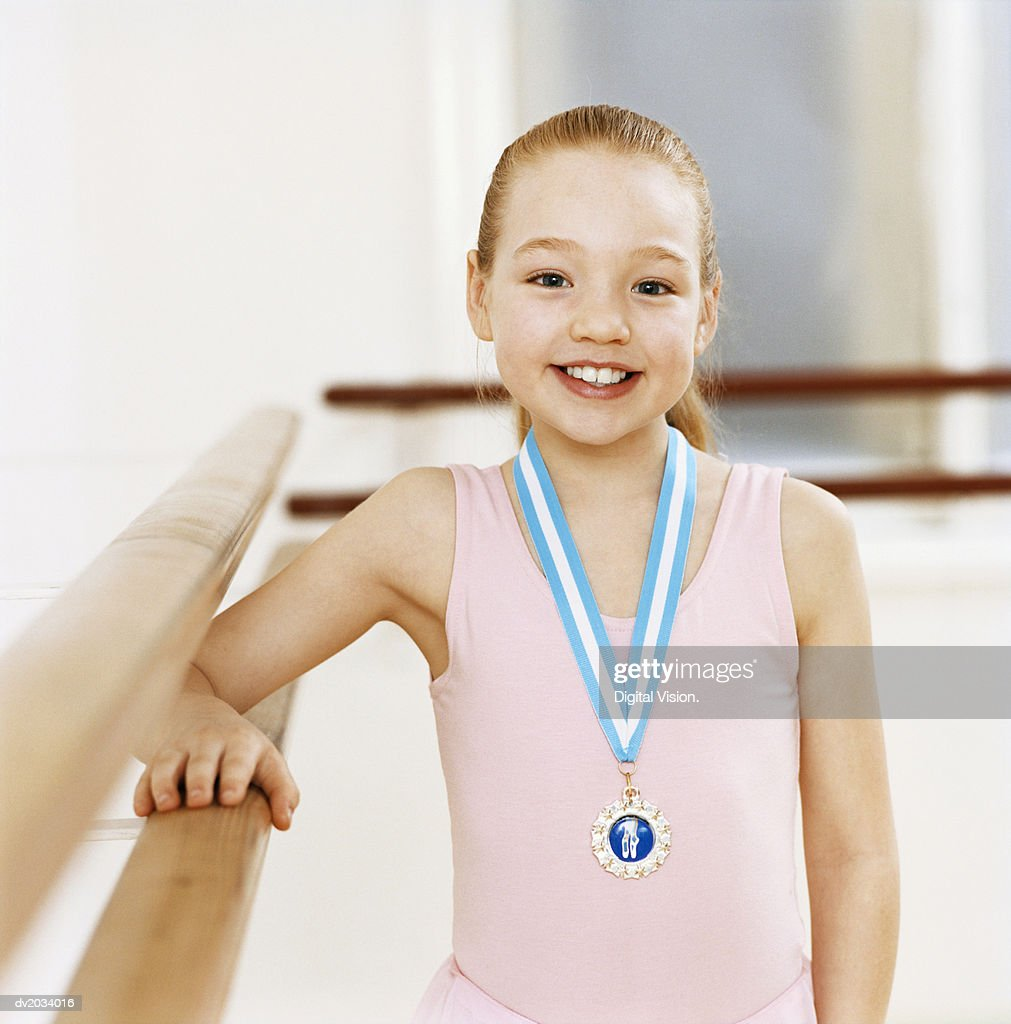 Portrait of a Young Ballet Dancer Wearing a Medal in a Dance Studio : Stock Photo