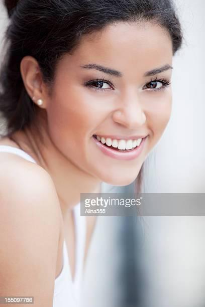 Portrait of a young beautiful Brazilian woman smiling outdoors