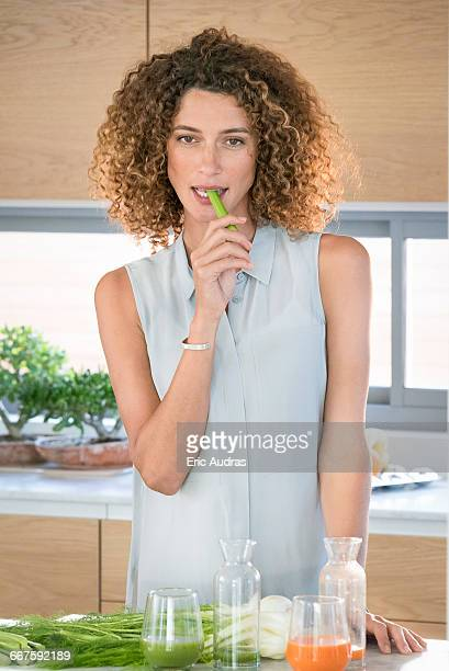Portrait of a young beautiful woman eating celery