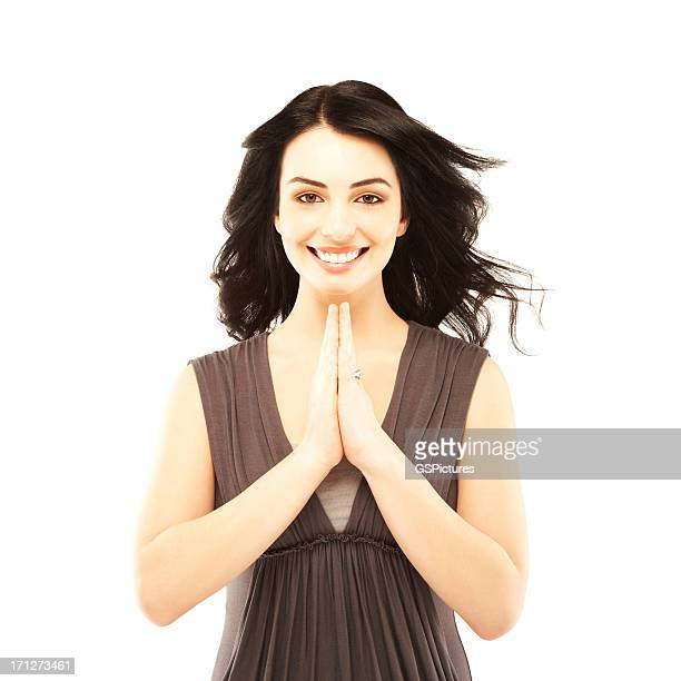 Portrait of a young beautiful woman isolated on white praying