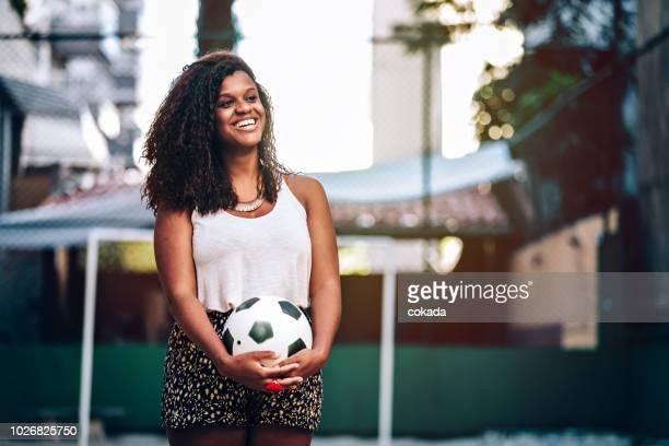 retrato de uma jovem mulher brasileira preto segurando uma bola de futebol no campo - latino americano - fotografias e filmes do acervo
