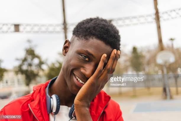 portrait of a young black man, laughing with hand on his face - verlegen stockfoto's en -beelden