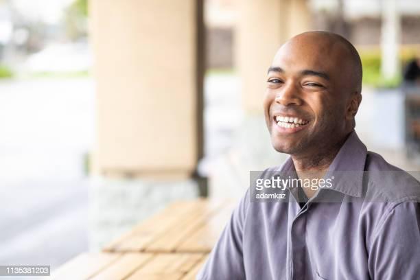 屋外笑顔の若い黒人男性の肖像 - テスティモニアル ストックフォトと画像