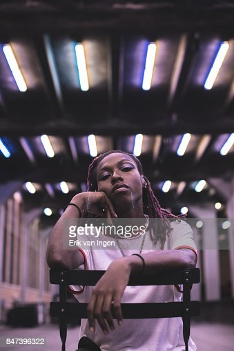 A portrait of a young, black woman sitting in a chair backwards.