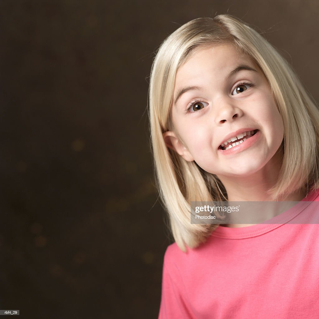 portrait of a young blonde caucasian girl in a pink shirt as she smiles big for the camera : Stockfoto