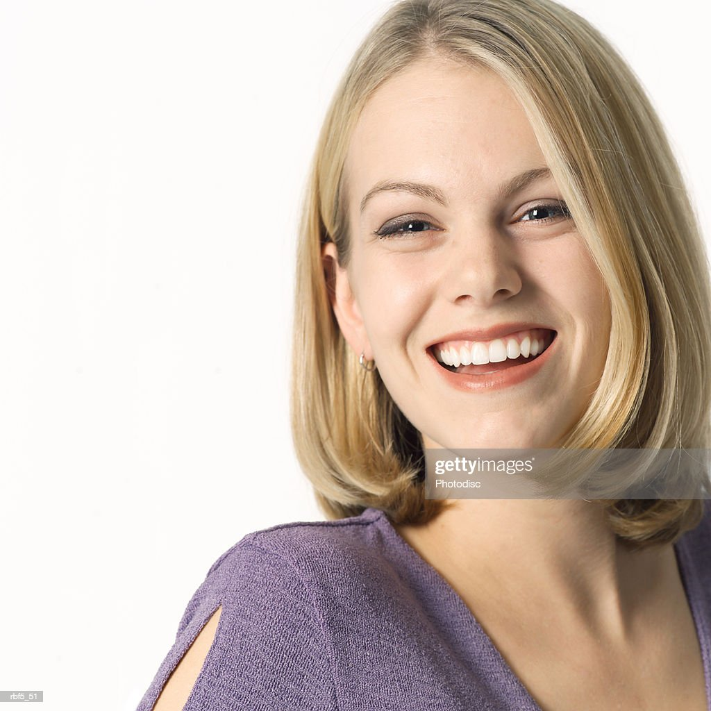 portrait of a young blonde caucasian woman in a purple blouse smiles and laughs into the camera : Stockfoto
