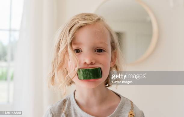 portrait of a young blonde girl with cucumber in her mouth - snack stock pictures, royalty-free photos & images