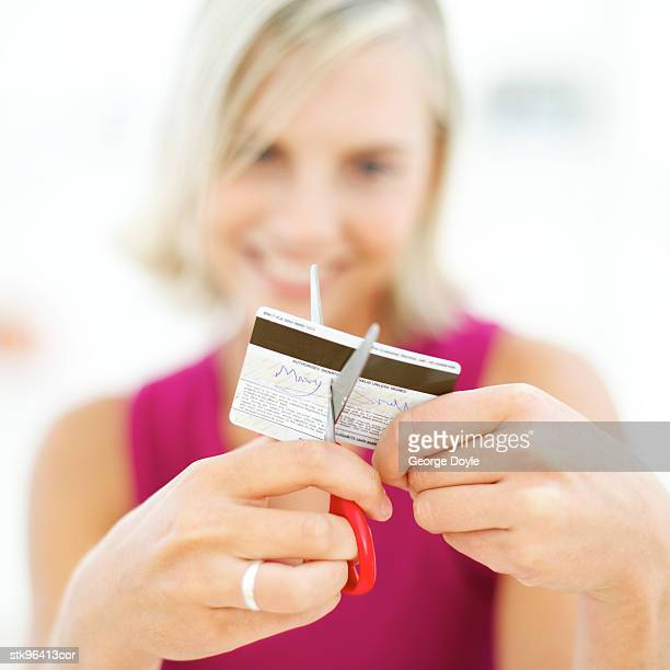 portrait of a young blonde woman destroying her credit card with a pair of scissors