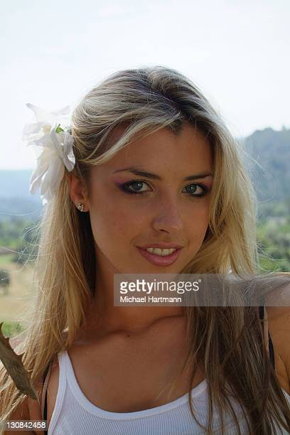 Portrait of a young, blonde woman in a palm tree garden, Mallorca, Balearic Islands, Spain, Europe