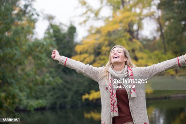 Portrait of a young blonde woman smilling breathable arms in the air at a lake in autumn.