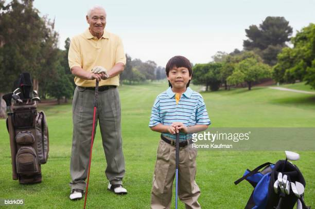 Portrait of a young boy and senior man standing together holding golf clubs