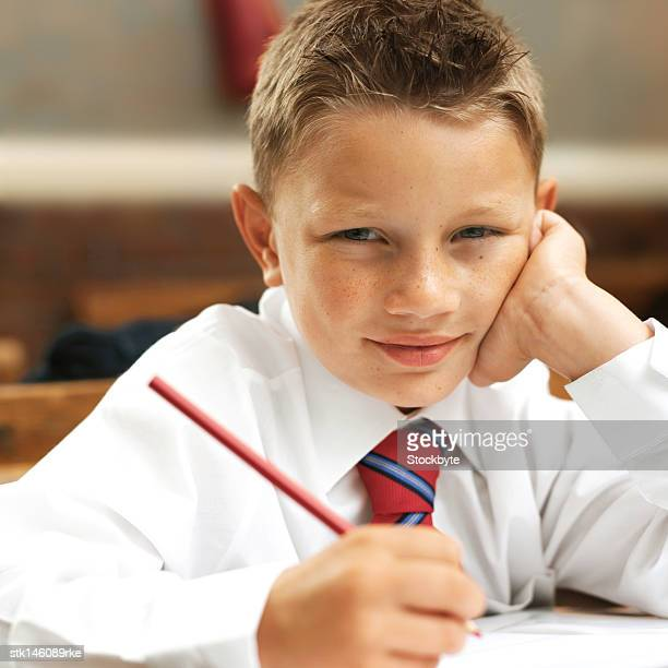 portrait of a young boy at school writing with a pencil